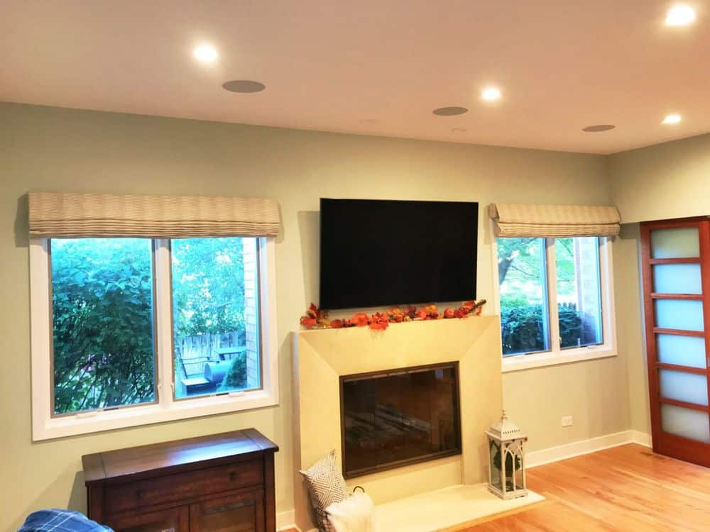 This living space features beige walls and hardwood floors, along with recessed ceiling lighting. There's a fireplace and a flat-screen TV on the wall, along with windows featuring Roman-style window shades.
