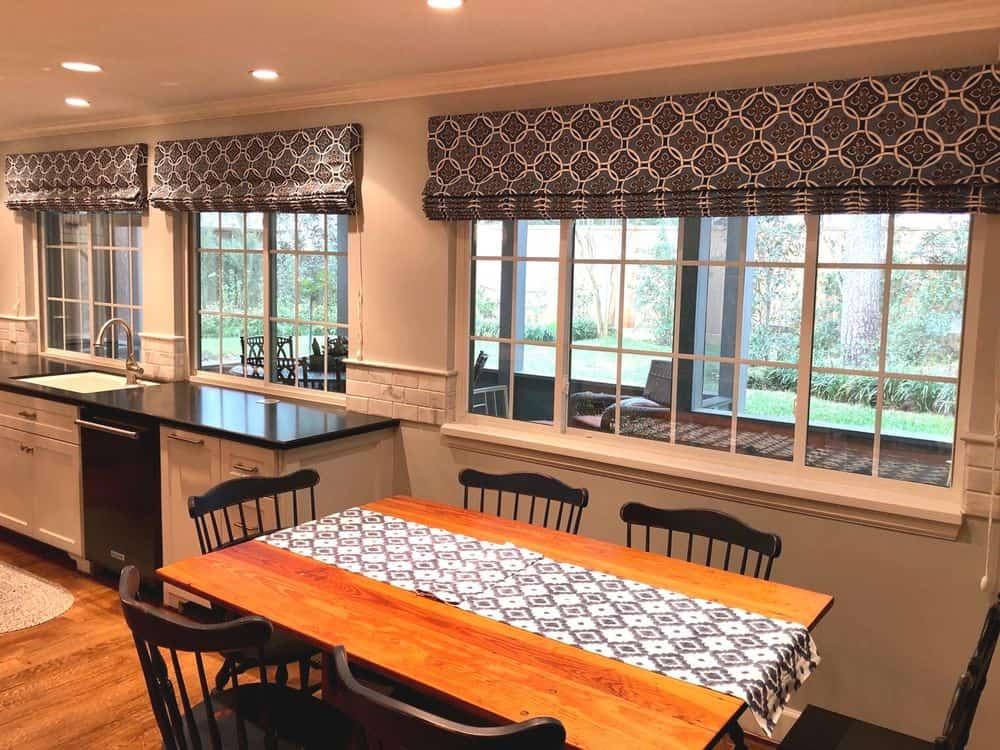 A dine-in kitchen featuring a single wall-style kitchen and a medium-sized rectangular dining table set for six. The windows in the area feature stylish window shades.