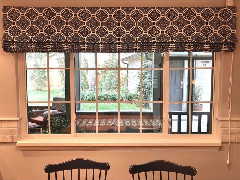 A closer look at this home's window featuring a stylish Roman-style window shade. The outdoor area can also be seen through this window.