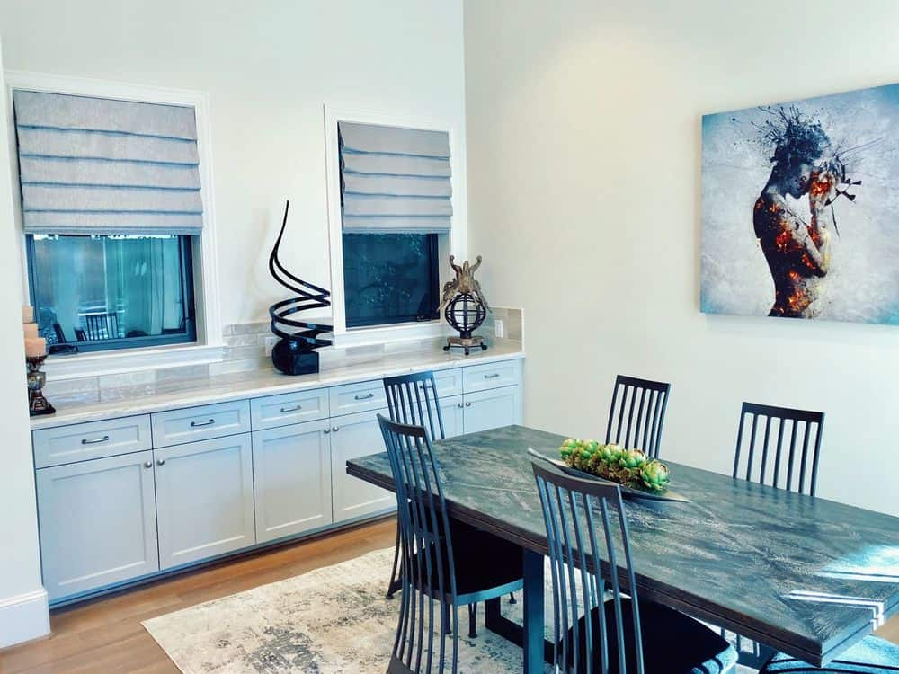 A dining area featuring a beautiful dining table and chairs set on top of an area rug covering the hardwood flooring. There's a marble top counter on the side featuring drawers.