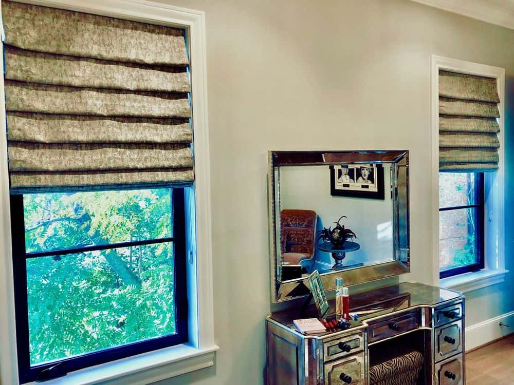 A focused look at this home's glass windows featuring Roman-style window shades. The area also has a desk table with built-in drawers.