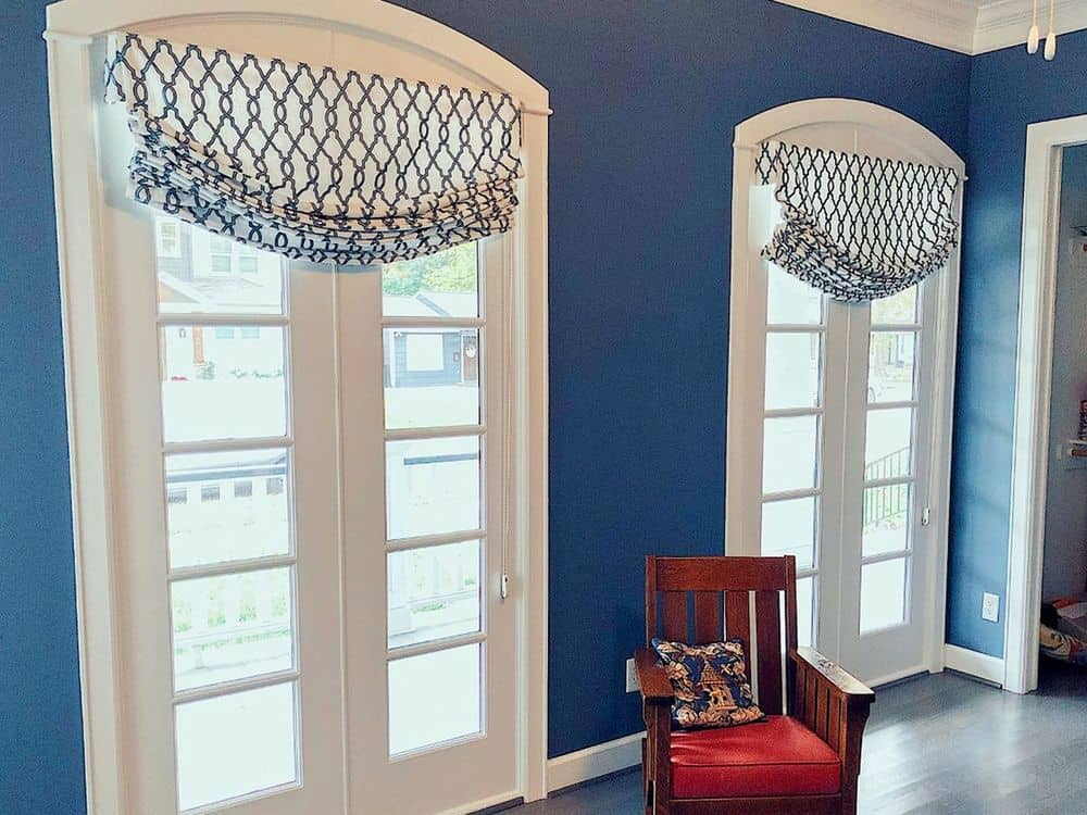 This home's entry features two doors with Roman-style shades. The area features blue walls and hardwood floors.
