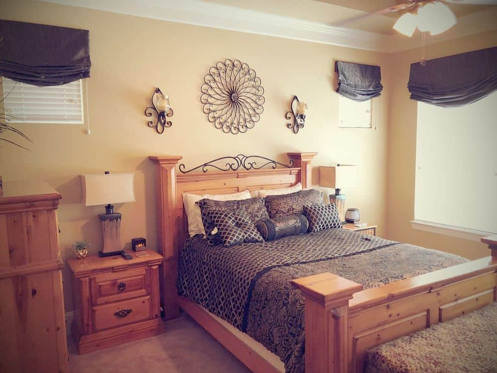 Master bedroom offering a wood-framed large bed along with a wooden side table and a wooden cabinet on the side. The room has beige walls and a tray ceiling with gorgeous ceiling lighting.