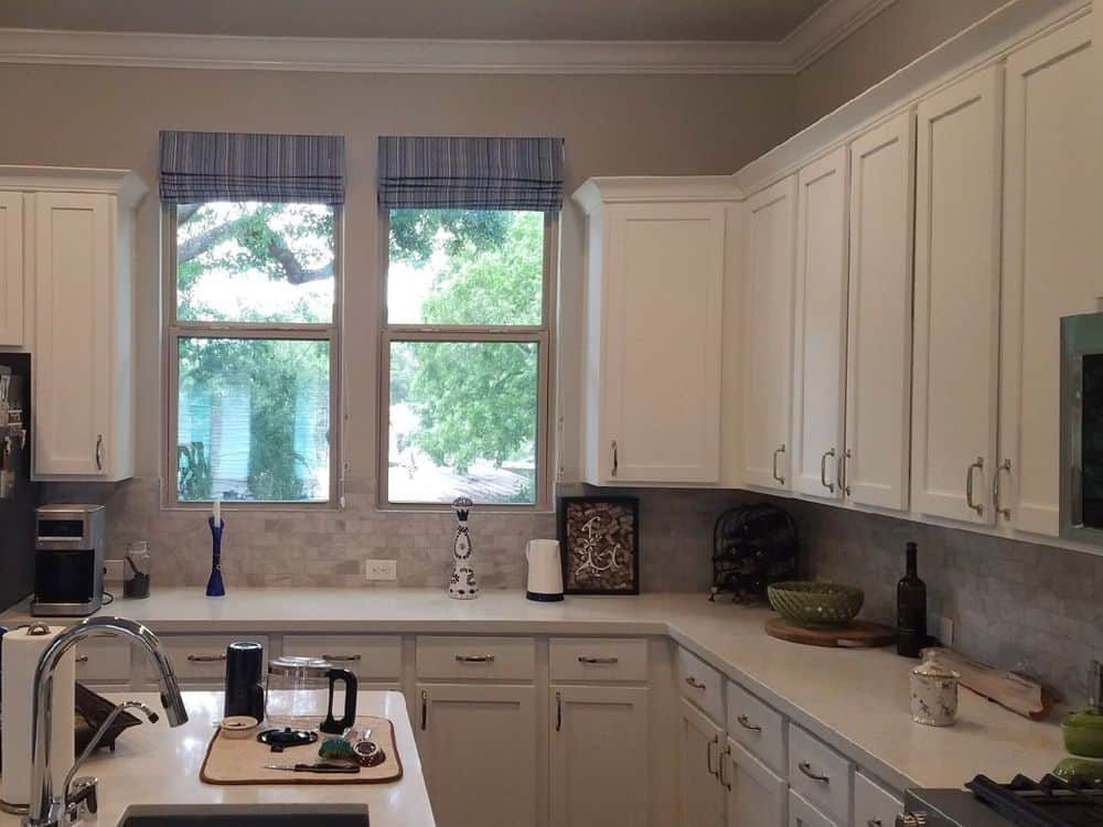 This kitchen features an L-shaped kitchen counter along with a white top center island and white kitchen cabinetry. The kitchen also has stylish tiles backsplash.