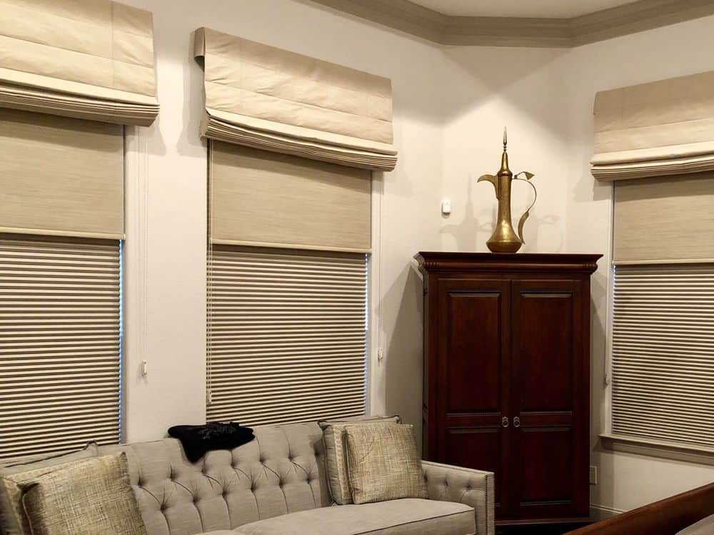 A living space featuring windows with Roman-style window shades. The room offers a cozy sofa set and a cabinetry in the corner.