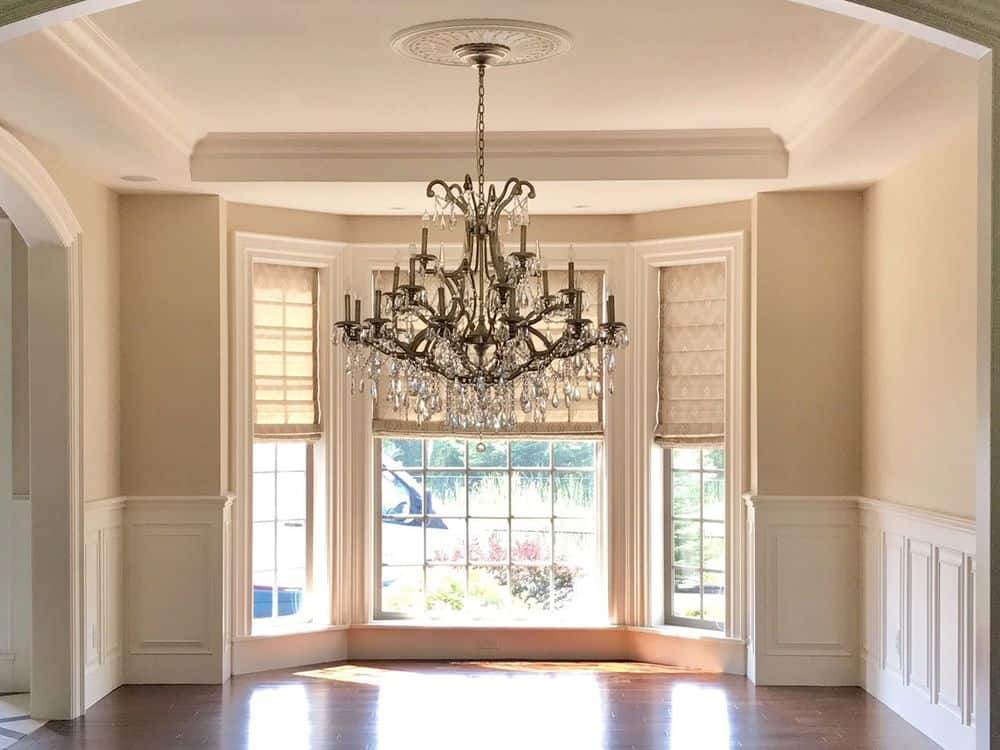 An empty living space boasting a glamorous chandelier hanging from the white tray ceiling. The home features hardwood floors and beige walls.