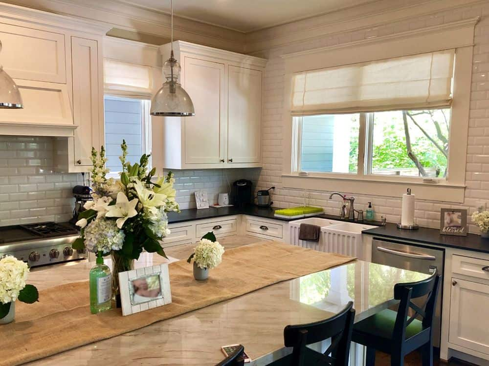 A kitchen with black countertops on its kitchen counters and a center island with a marble countertop and has a breakfast bar lighted by pendant lights. The kitchen has tiles backsplash as well.
