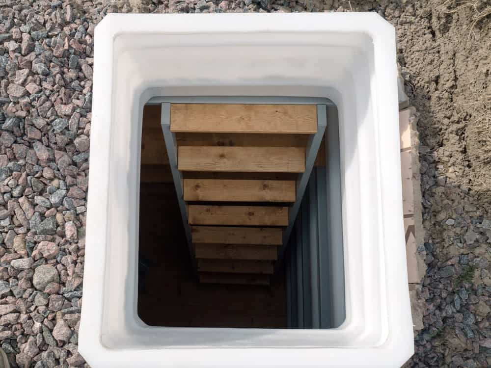 A downstairs way to this home's root cellar. The staircase is a straight-type with wooden steps, matching the hardwood flooring.