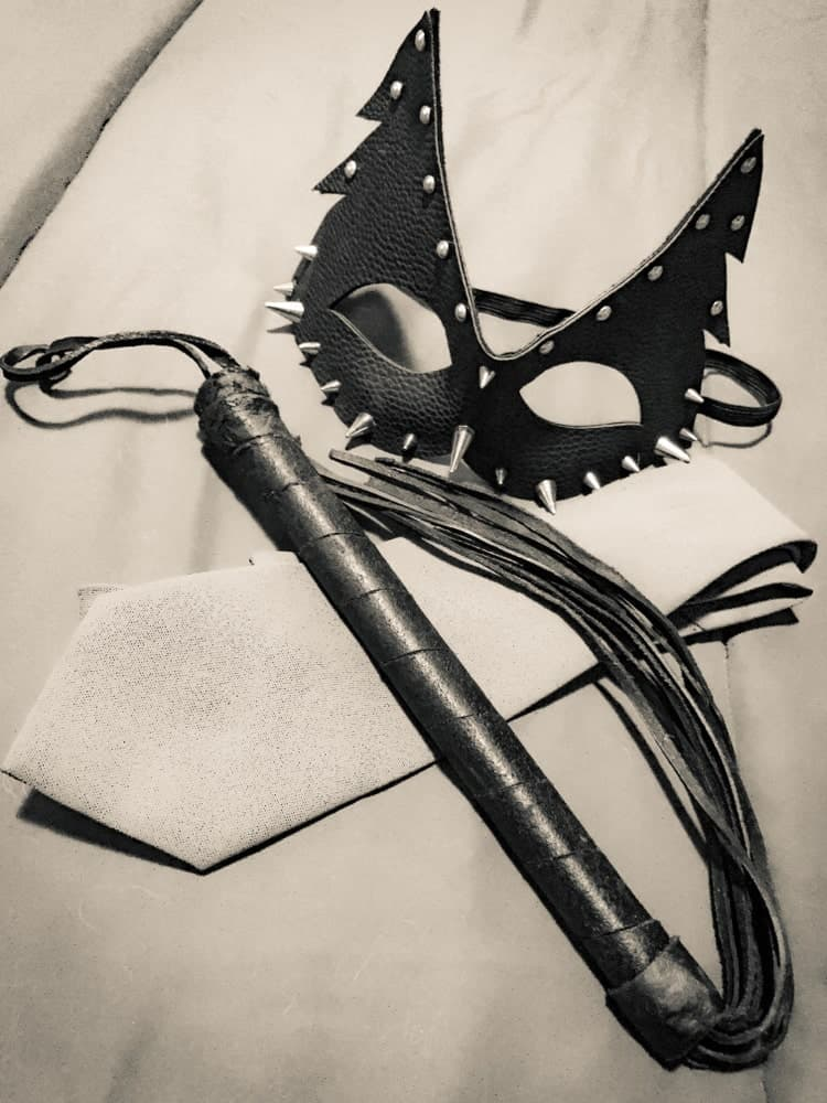 Shades of pain with a leather mask, leather whip, and a white necktie.