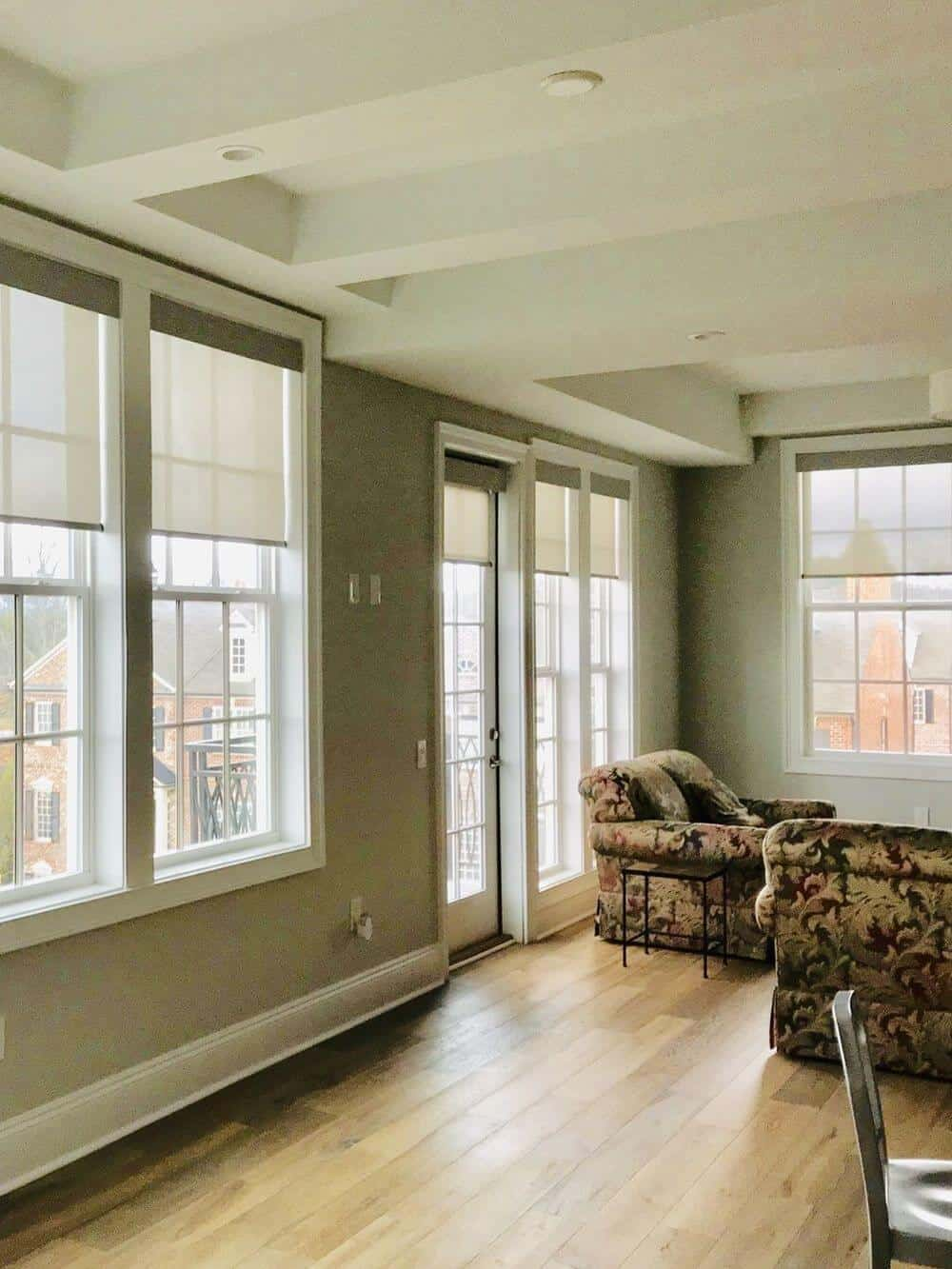 This great room boasts a set of elegant living space seats and a dining table set nearby. The room has a stunning white custom ceiling and gray walls, along with hardwood flooring.