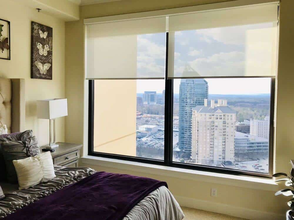 Medium-sized primary bedroom offering a very comfy bed set lighted by a white table lamp. The room also has large glass windows featuring solar shades.