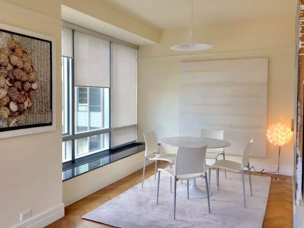 A nice dining room featuring a white dining table and chairs set on top of an area rug covering the herringbone-style hardwood floors. The room is surrounded by white walls and glass windows with solar shades.