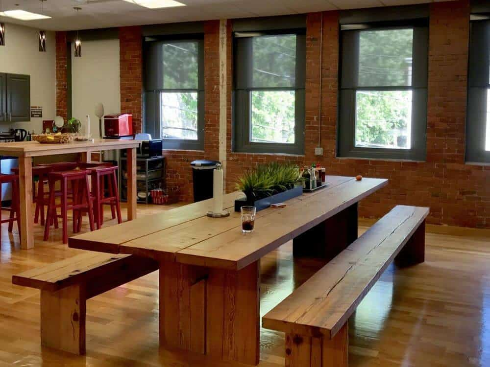 A spacious dining room boasting a wooden dining table and bench seats set along with hardwood flooring and brick walls. The room also has windows featuring solar window shades.