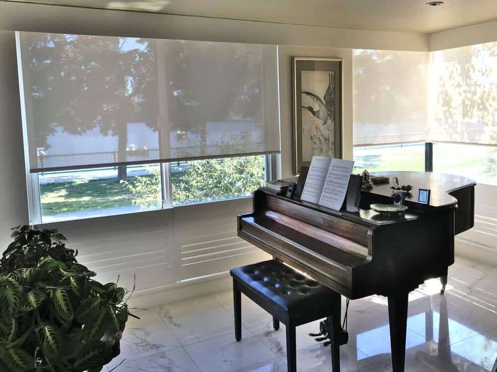 A focused look at the side of this home where the classy piano is set. The home features marble tiles flooring and glass windows featuring solar shades.