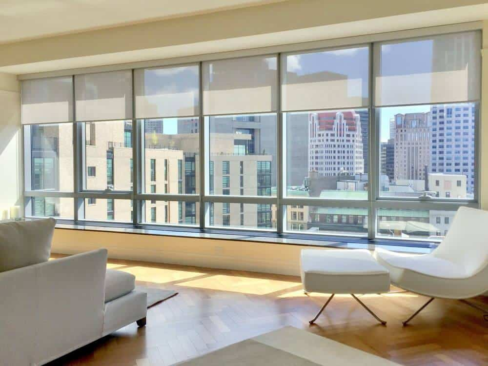 A spacious living room boasting herringbone-style hardwood floors, beige walls and a modish sofa set, along with glass windows featuring solar window shades.