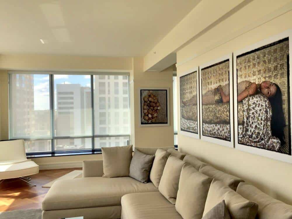 This living space boasts a large L-shaped sofa set along with a striking wall decor set at the back. The area features stylish hardwood floors and glass windows with solar shades.