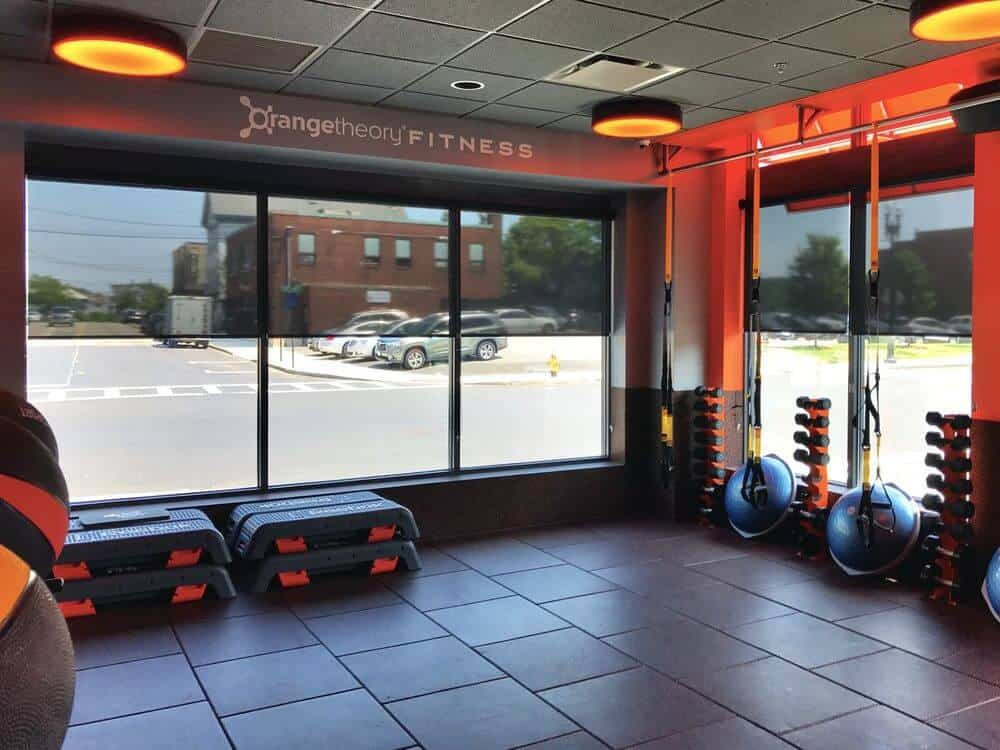 This fitness gym boasts tiles flooring and tiled ceiling, along with stylish orange walls and large glass windows with solar window shades.