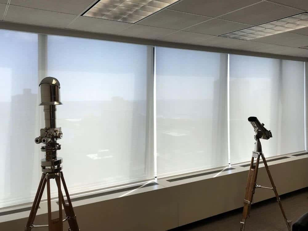 A focused look at this office room's large glass windows featuring solar window shades. The room has tiles flooring and tiled ceiling.
