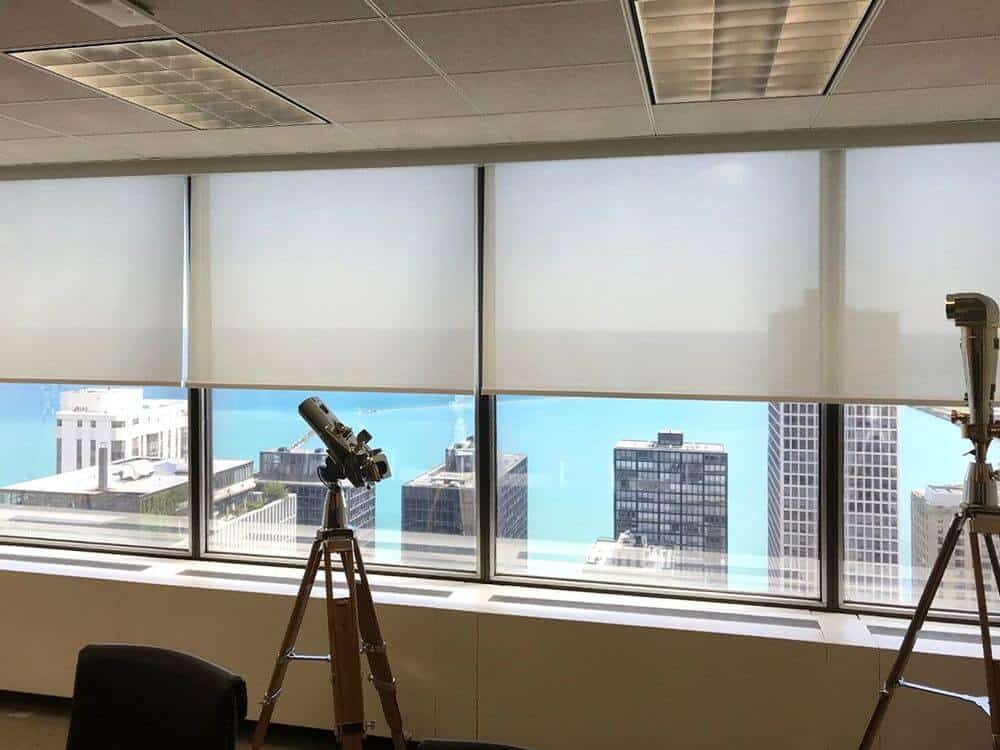 A focused look at this room's modern glass windows featuring solar shades. The room offers a stunning view of the city from above the building.