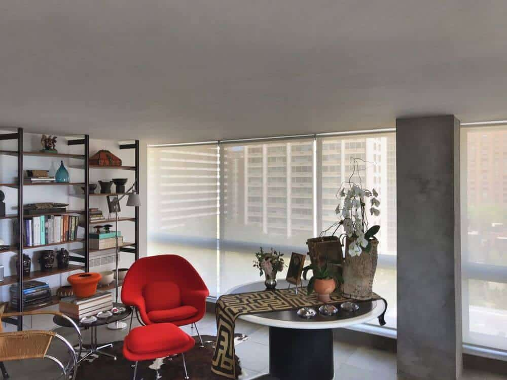 This home boasts stylish seats and a round centerpiece table, along with large freestanding shelf. The room also features glass windows with solar window shades.