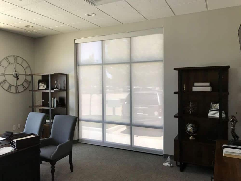 A spacious home office featuring light gray walls, carpet floors and a tiled ceiling with recessed ceiling lights. The room offers desks and modern chairs, along with freestanding shelving.