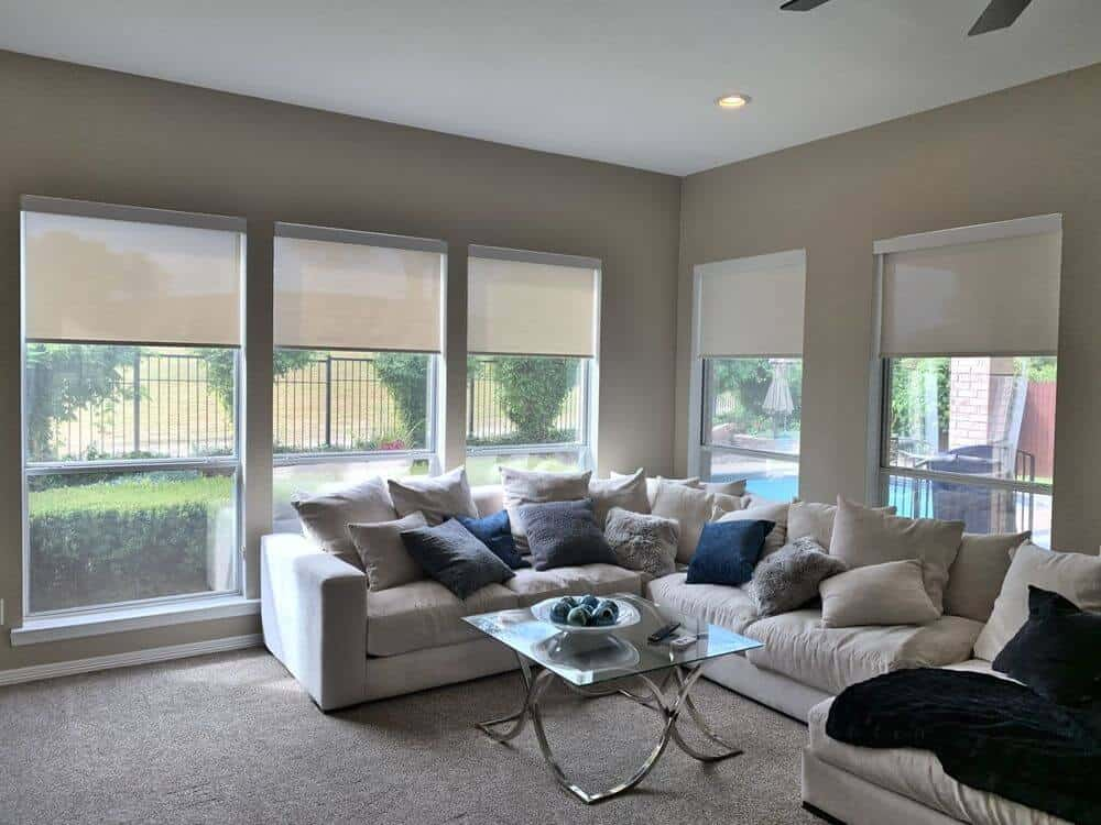 Living space offering an L-shaped sofa set that looks absolutely comfortable. There's a classy glass top center table as well. The room features carpet flooring and gray walls, along with glass windows with solar shades.