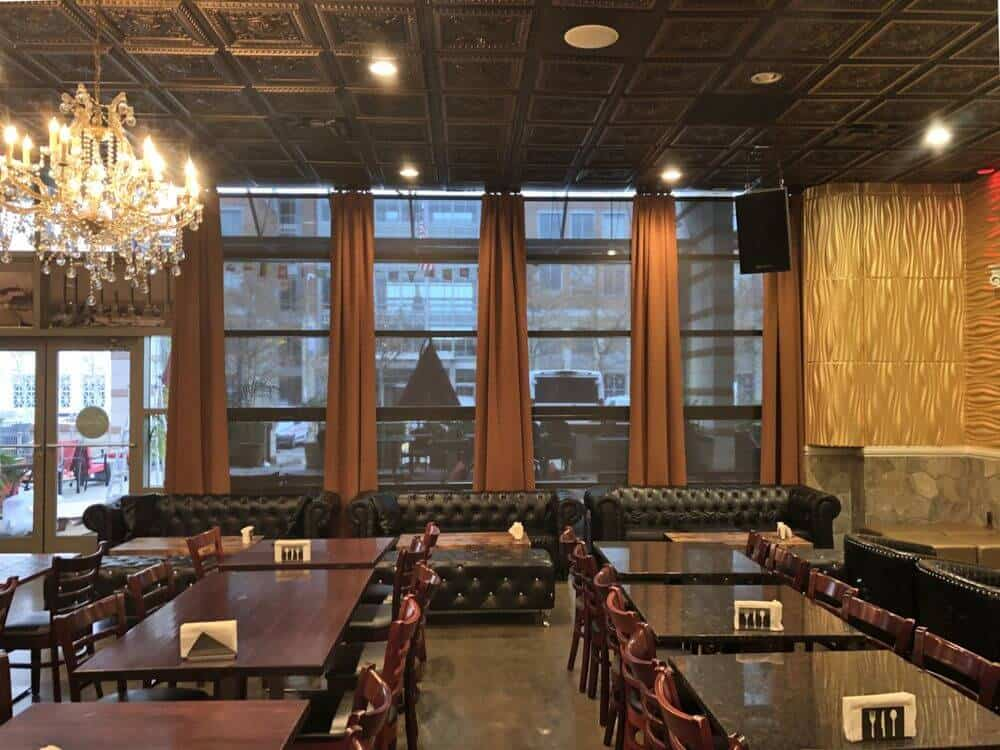 A beautiful restaurant boasting classy dining table sets along with elegant black leather couches. The building boasts a custom decorated ceiling lighted by a glamorous chandelier.