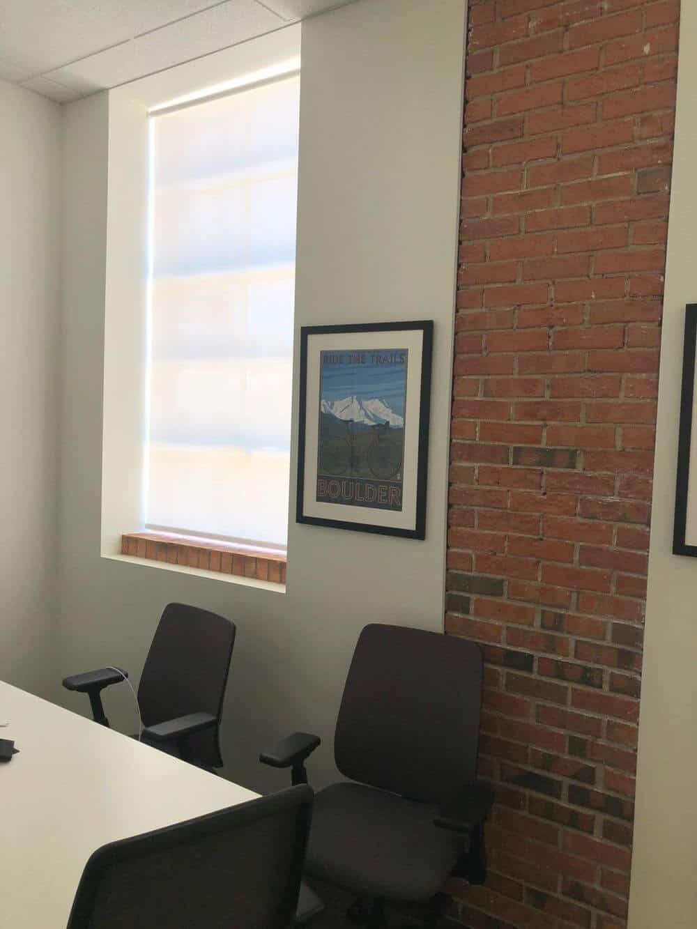 This office room boasts a simple office table paired with modern office chairs. The room features custom ceiling and walls, along with glass windows featuring solar shades.