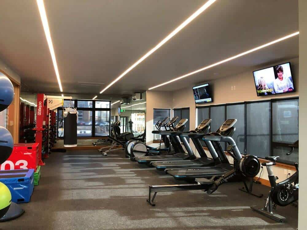 A spacious gym boasting well-maintained machines and other equipment, along with two TVs on the wall and stylish ceiling lighting, along with carpeted flooring.