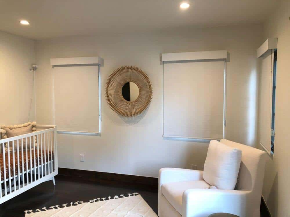 A nursery room featuring dark hardwood flooring and white walls, along with a regular ceiling with recessed ceiling lights.