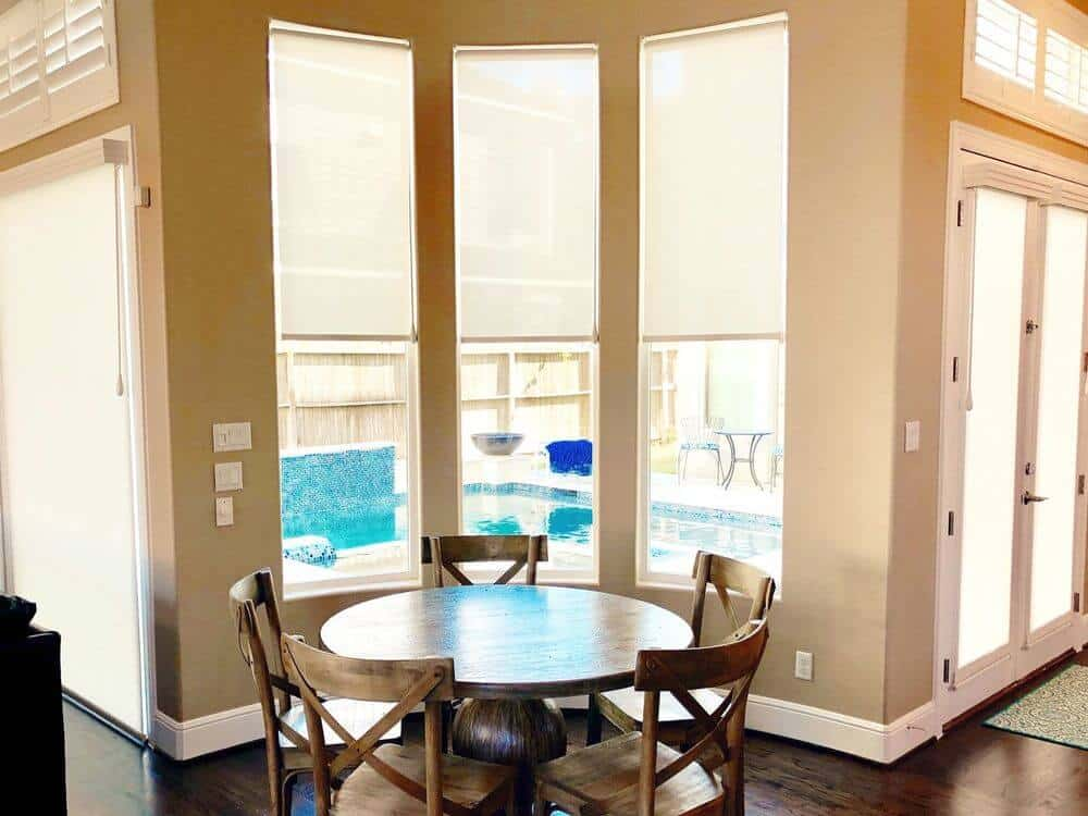 A look at this round dining nook with wooden chairs, set near the vertical glass windows with solar window shades. The home features beige walls and hardwood floors, along with a tall ceiling.