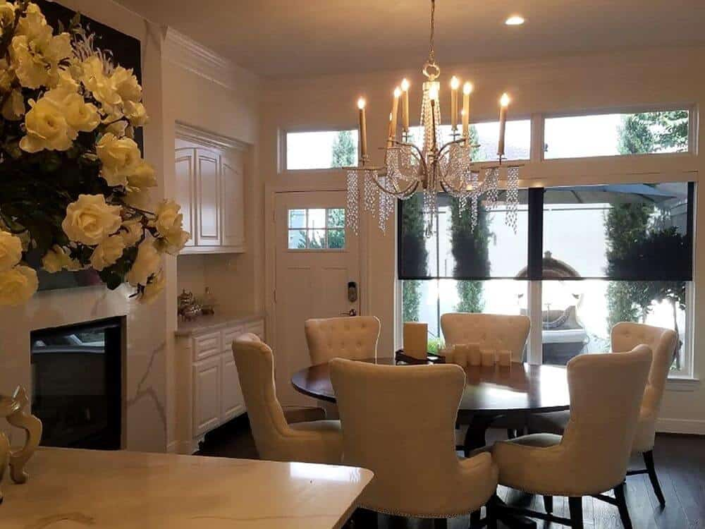 A dine-in kitchen boasting a classy dining table and chairs set lighted by an elegant chandelier. The area features a fireplace and a large widescreen TV on the wall.