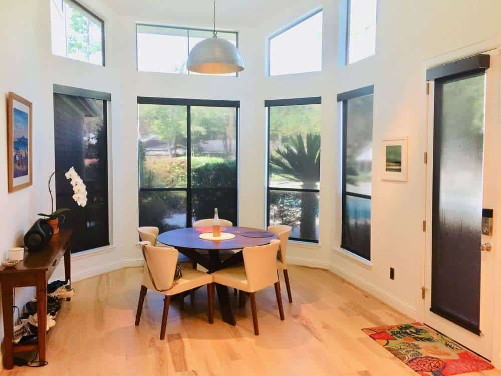 A spacious dining area featuring a round dining table set. The room has hardwood floors and a tall ceiling together with white walls and glass windows with solar shades.