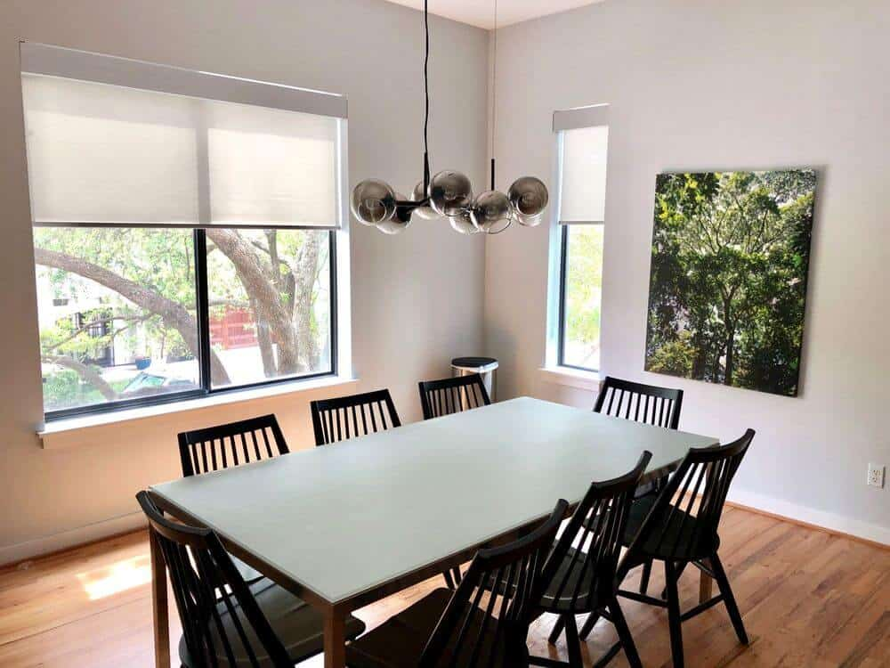 This home offers a dining room featuring a stylish dining table set lighted by a modish ceiling light. The room features white walls and glass windows with solar shades.