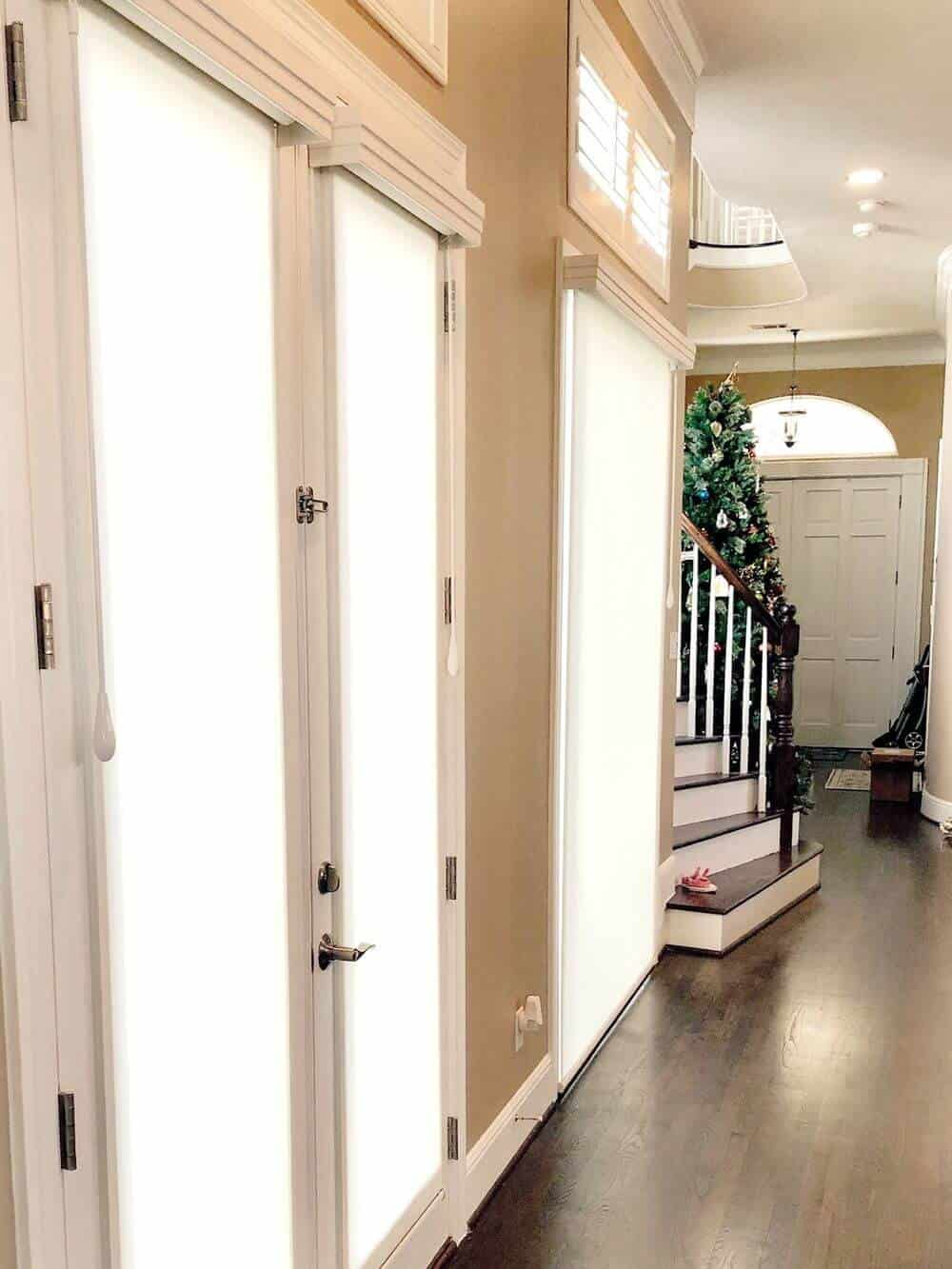A home's entry featuring beige walls and hardwood floors, along with a tall ceiling. The staircase is set on the side, leading to the home's second floor.