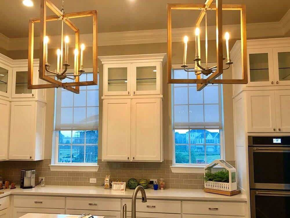 This kitchen features white kitchen counter and white cabinetry, along with a small white center table lighted by charming chandeliers.