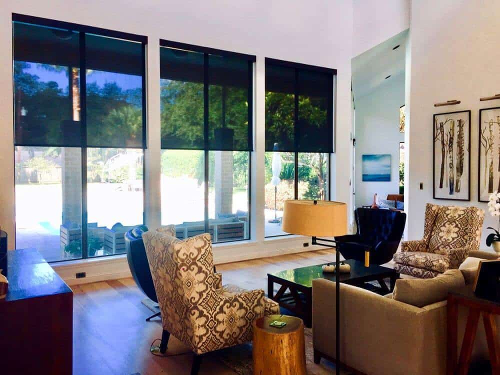 Living space featuring a set of elegant seats and a stylish area rug covering the well-polished flooring. The area has white walls and a white tall ceiling, along with vertical glass windows featuring solar window shades.