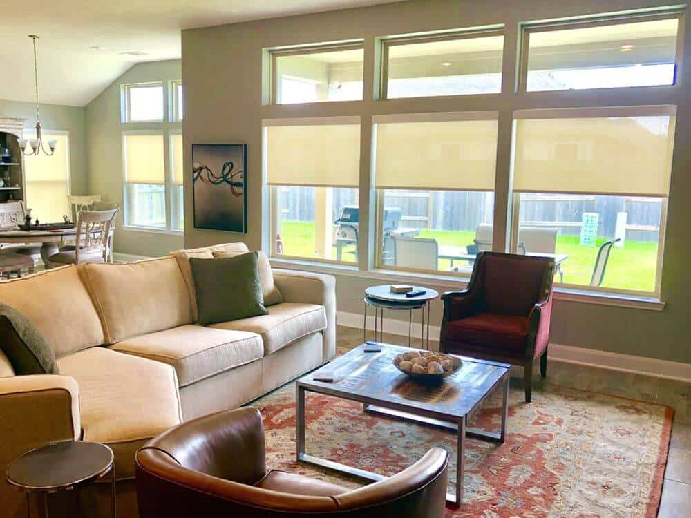 A look at this living space's classy sofa set on top of a large area rug. The area features a living space, a dining nook and a kitchen.