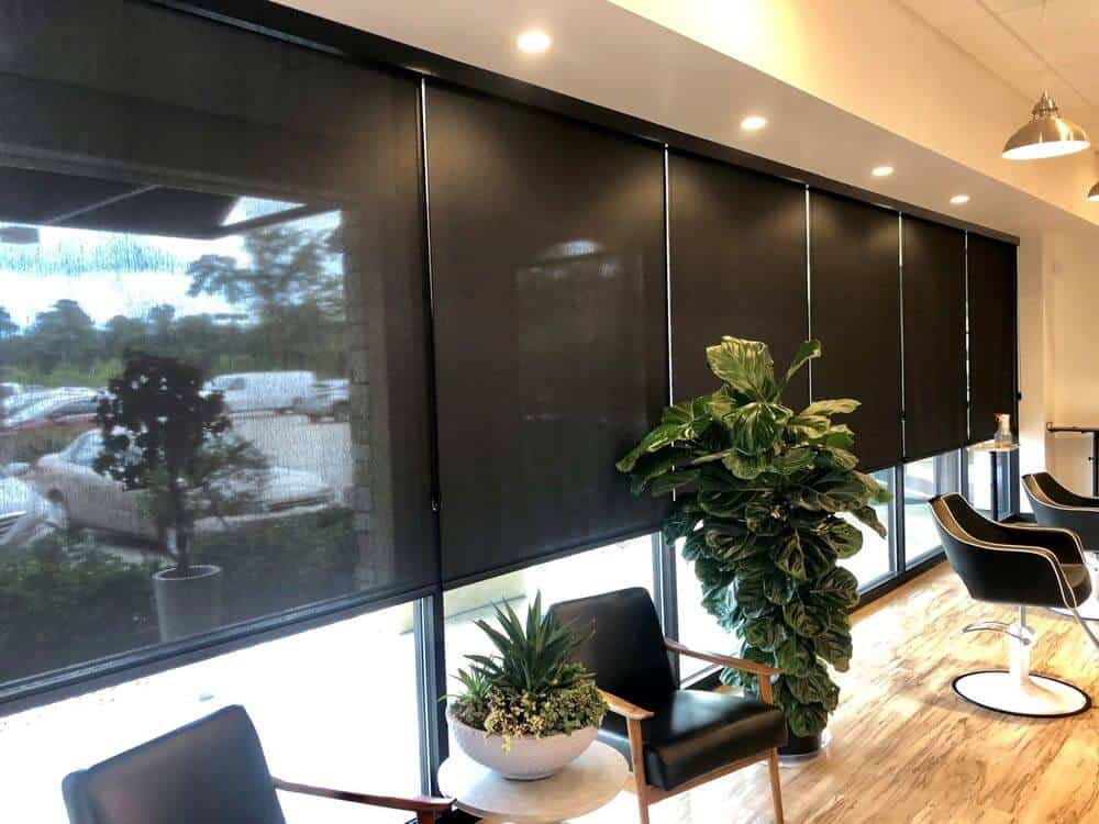 A large office room boasting large glass windows featuring black solar window shades, modern seats and a custom ceiling.