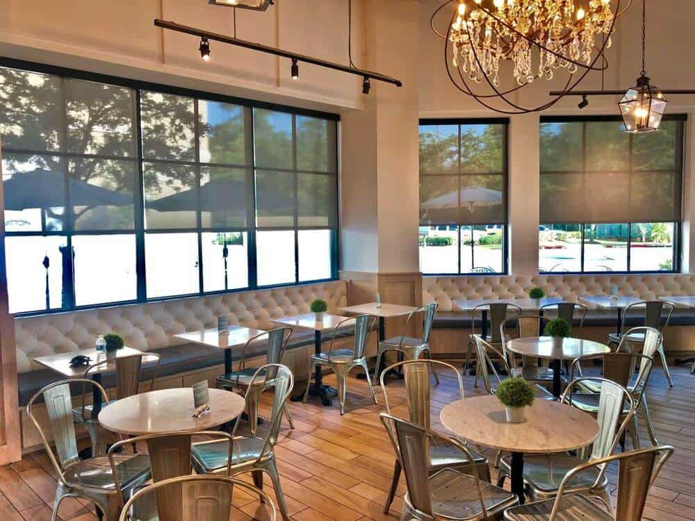 This restaurant boasts classy dining table sets. The area is lighted by pendant lights and track lights, along with a glamorous chandelier. The building's windows feature solar shades.