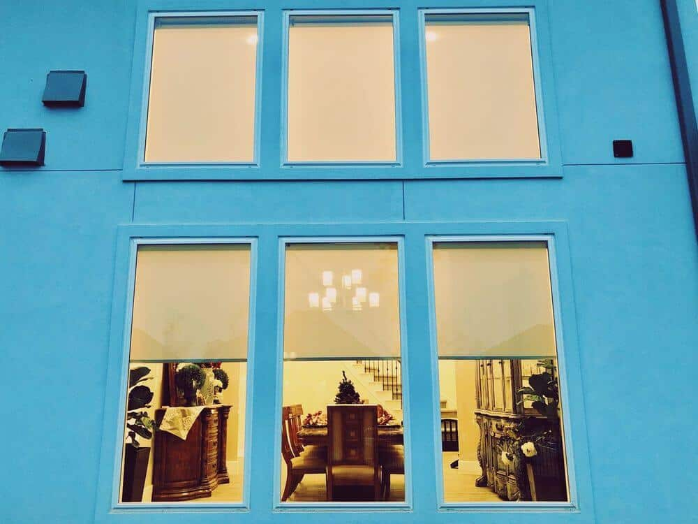 A view of this home's glass windows with solar shades from outside of the house. The house exterior is painted in light blue.