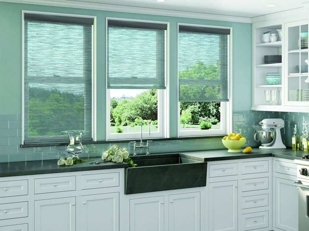 This kitchen offers an L-shaped kitchen counter with green tiles backsplash and green walls, along with white cabinetry and shelving. The windows in the area also feature stylish solar shades.