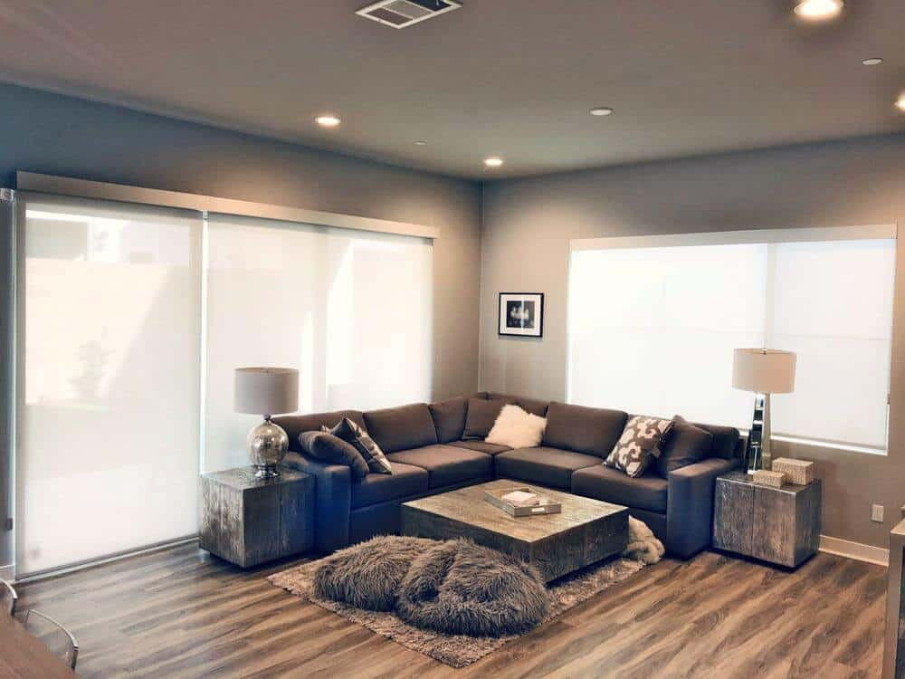 A spacious living space offering a modern L-shaped sofa set along with a pair of stylish side tables with a matching center table. The area is surrounded by gray walls and ceiling, along with attractive hardwood flooring.