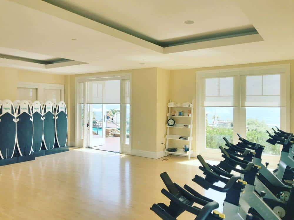 A spacious home gym featuring well-polished flooring and a custom tray ceiling, along with beige walls and windows with solar window shades.