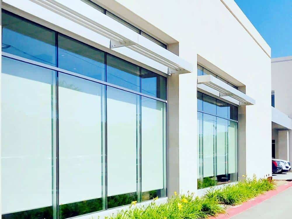 A look at this building's white exterior with well-maintained lawns and large glass windows featuring solar window shades.