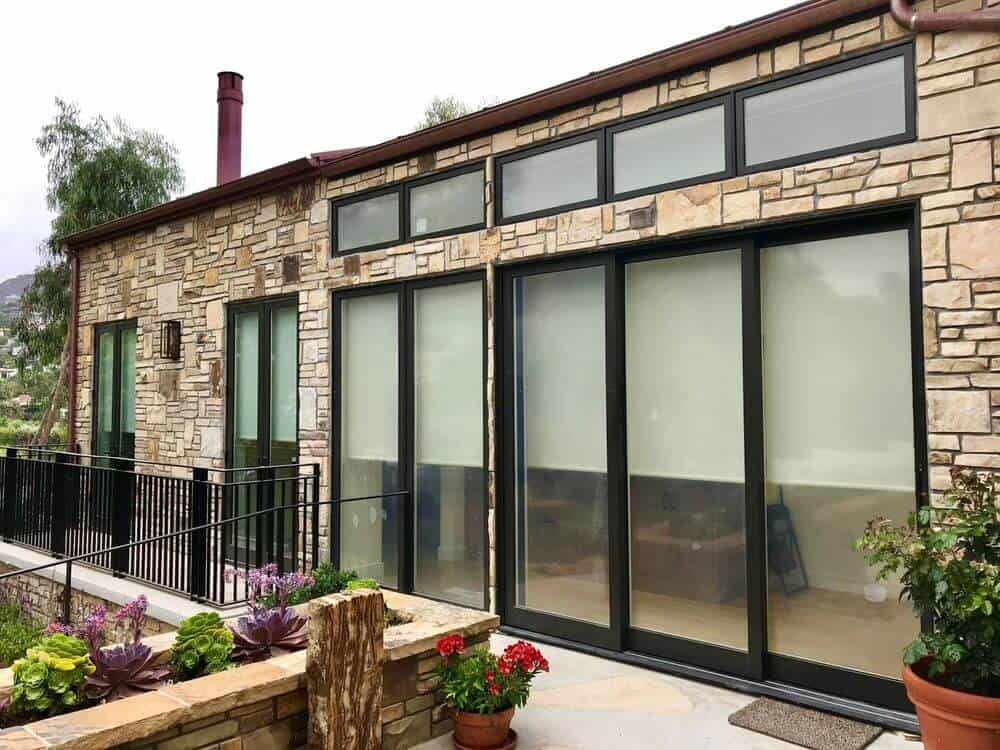 A look at this house's exterior made of stone and glass. The home has a balcony area filled with colorful plants and flowers.
