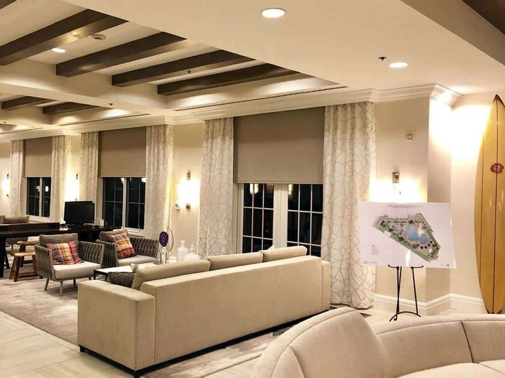 Large great room featuring modern living set and a custom tray ceiling. The room features stylish area rugs and charming wall lights.