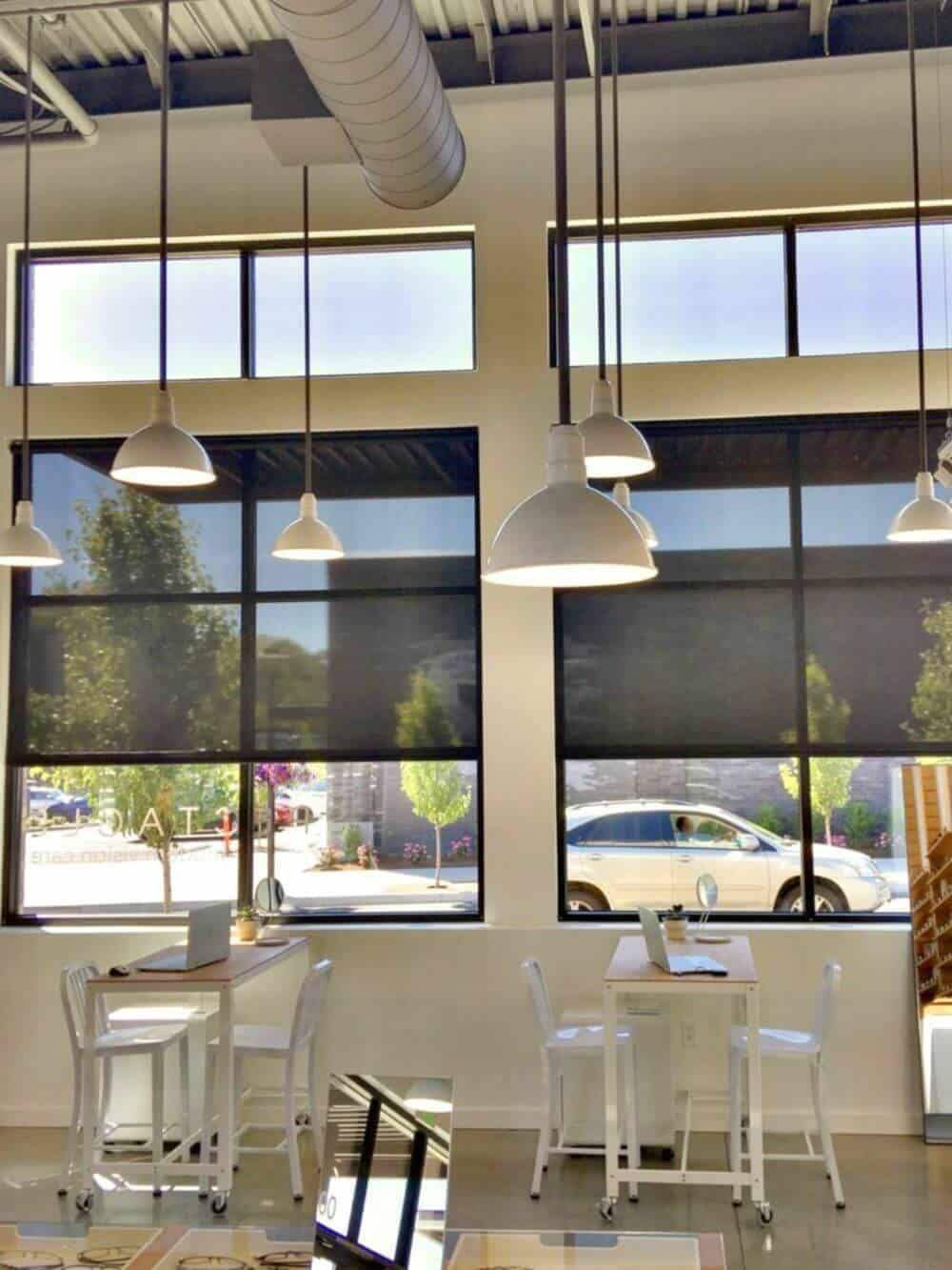 A dine-in area of the restaurant featuring multiple table sets and a tall ceiling with several pendant lights. There are glass windows as well with solar window shades.