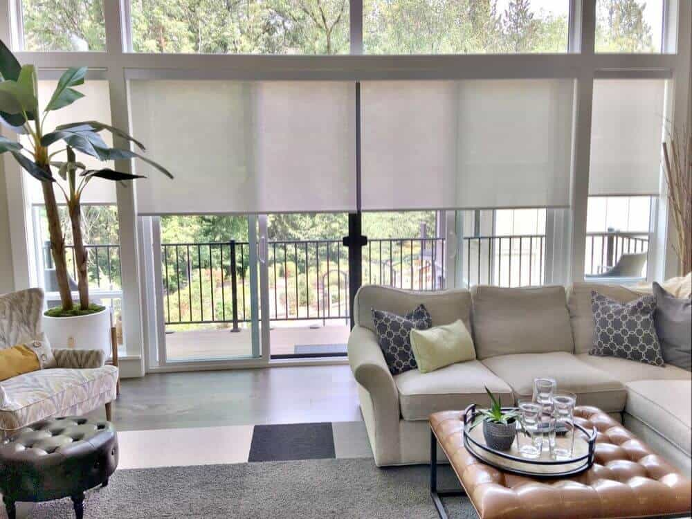 A living space featuring a classy sofa set and gray flooring topped by a stylish area rug. There's a doorway leading to the outdoor area.