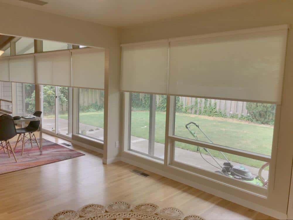 A focused look at this home's windows featuring solar window shades. The area is where the dining table and chairs are set. The flooring is topped by stylish area rugs.
